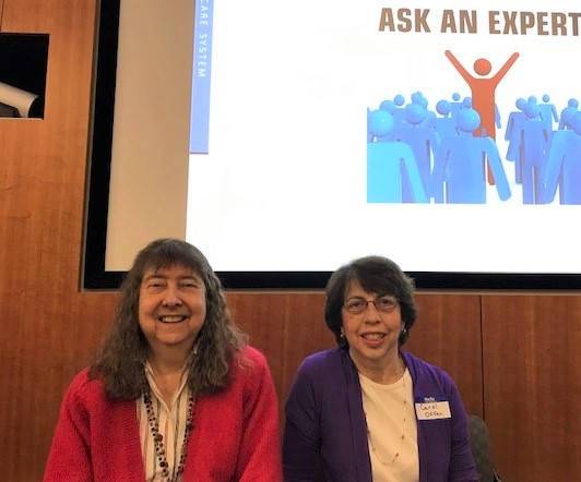 "the 2 authors, women, sitting in front of a sign that says ""Ask the Expert"""