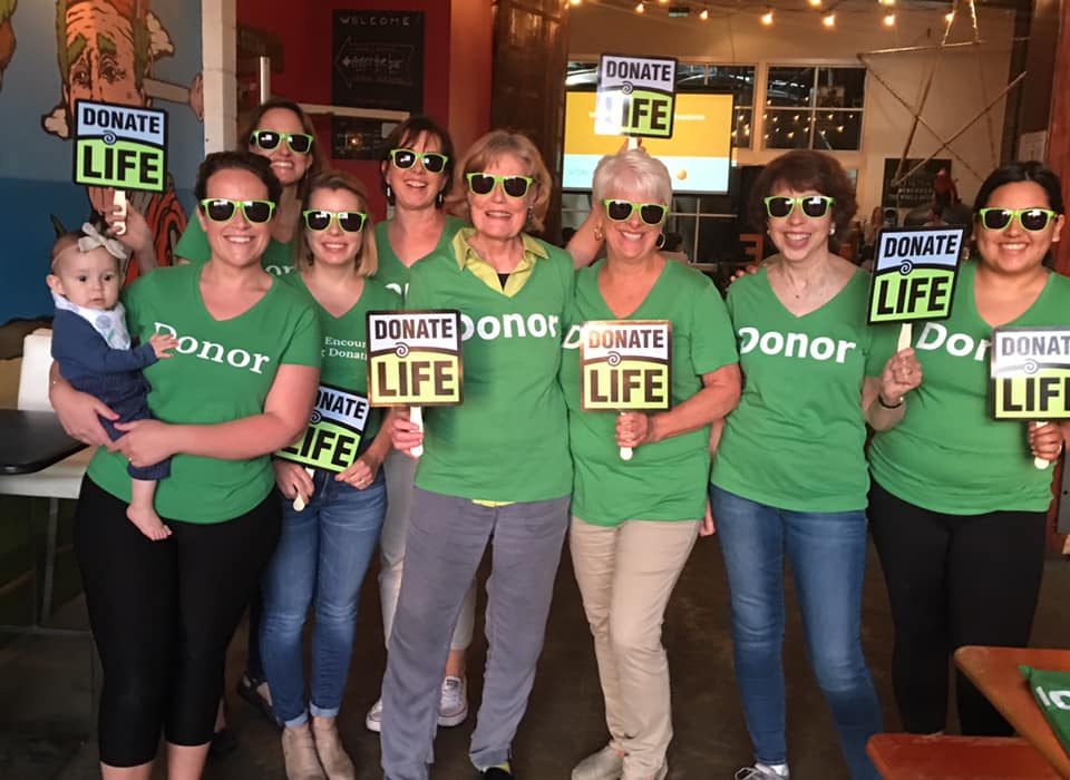 "A picture of WELD members wearing DONOR tee shirts and holding signs that say ""Donate Life."" The caption tells where Michele is standing."
